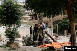 FILE - Members of the Islamist rebel group al-Nusra Front prepare a homemade mortar in the Bustan al-Qasr neighborhood of Aleppo, Syria, June 5, 2014.
