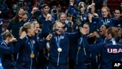 The U.S. team celebrates after winning the women's Volleyball World Championships final match against China in Milan, Italy, Oct. 12, 2014.