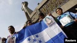 Mujeres centroamericanas sostienen una bandera hondureña frente a la Basílica de Guadalupe, en México, D.F.