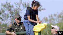 Agentes de la patrulla fronteriza ayudan a una muchacha en el Sur de Texas. El congreso realizará una audiencia este martes para analizar los desafíos en la frontera.