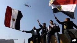1月25日部分埃及民众在解放广场向天空飞过的军用直升机挥舞国旗