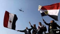 FILE - Egyptians wave national flags as they greet an army helicopter flying over Tahrir Square.