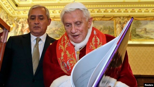 Pope Benedict XVI exchanges gifts with Guatemala's President Otto Perez Molina during a private audience at the Vatican February 16, 2013.