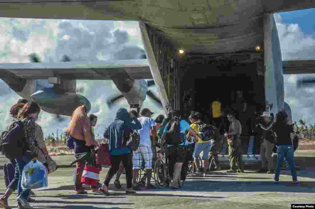 Philippine citizens board an HC-130 Hercules to be airlifted to safety. (U.S. Navy)