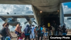 2013年11月17日,菲律宾的灾民登上美国海军直升机离开灾区。(美国海军提供)