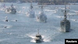 FILE - Royal Australian Navy warships led by HMAS Sydney (R) enter Sydney Harbor as part of the International Fleet Review celebrations, Oct. 4, 2013.