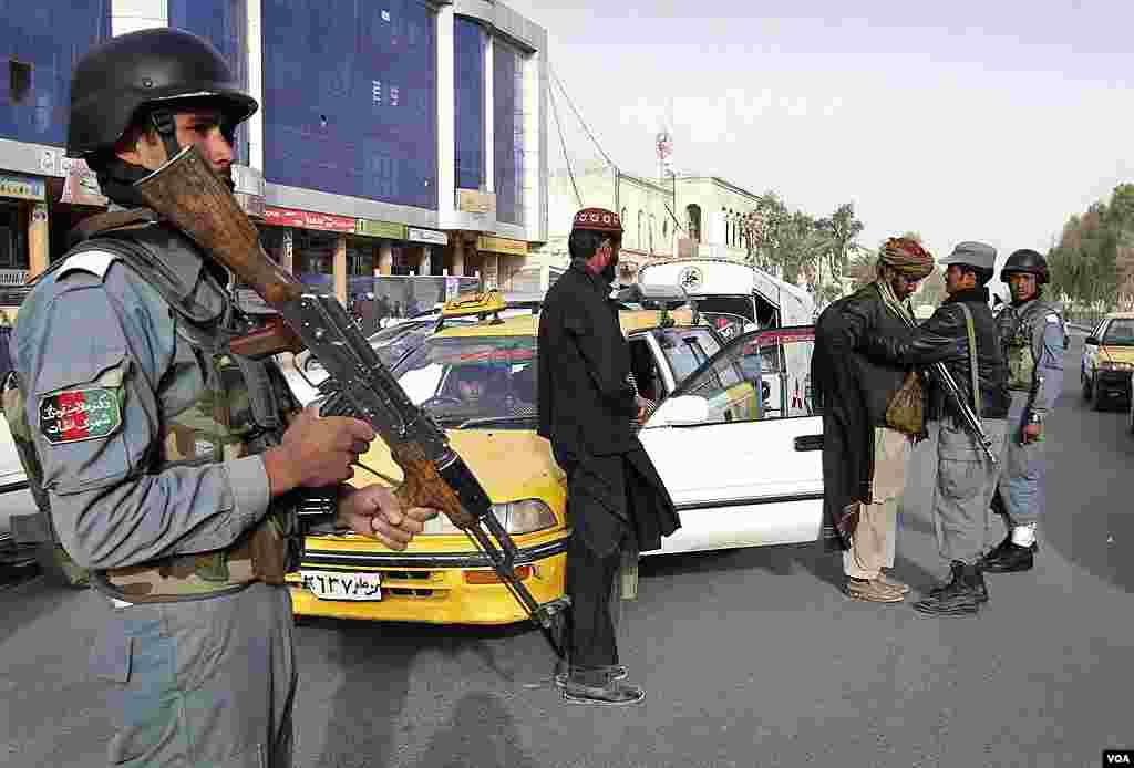 An Afghan policeman, left, stands guard as a colleague, right, searches a taxi passenger at a police checkpoint following the killing of civilians by a U.S. soldier in Kandahar province, March. 12, 2012. (AP)