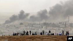 在叙土边界的叙吕奇郊外,人们站在山坡上观看叙利亚科巴尼的战火硝烟。(2014年10月13日)