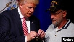 Donald Trump conversa con el Coronel Louis Dorfman, quien le regaló una medalla Corazón Púrpura, en la escuela Briar Woods High School de Ashburn, Virginia.