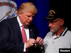 FILE - Republican U.S. Presidential nominee Donald Trump talks to Lt. Col. Louis Dorfman, who gave Trump his Purple Heart, during a campaign event at Briar Woods High School in Ashburn, Virginia, Aug. 2, 2016.