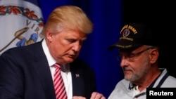 共和党总统候选人川普在维吉尼亚州阿什本的一个竞选活动中和送他紫心勋章的退伍中校路易斯·多夫曼交谈(2016年8月2日)
