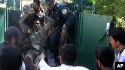 Seorang tentara Afghanistan yang luka parah dalam penyerbuan Taliban ke gedung pengadilan di provinsi Farah diangkut oleh rekan-rekannya (3/4).