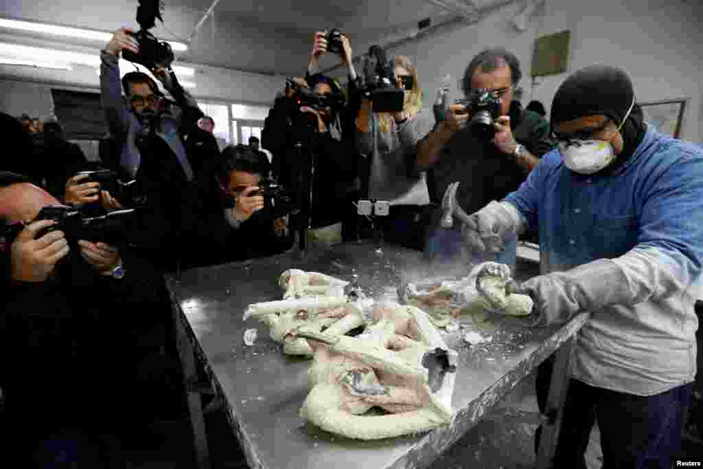 """A worker cracks the mold of """"The Actor"""" statuette during a media event on the production of the statuettes for the 24th annual Screen Actors Guild Awards at American Fine Arts Foundry in Burbank, California, Jan. 9, 2018."""