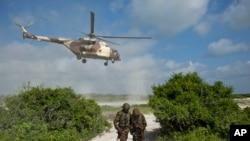 Deux soldats somaliens regardent l'arrivée d'un hélicoptère kényan, à Bur Garbo, Somalie, le 14 décembre 2011.