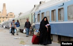 Passengers walk beside a train in a the rail station in Baghdad, May 6, 2013.