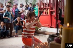 Seorang umat Buddha sedang berdoa sementara para tetangganya memperhatikan di Banda Aceh, 19 Februari 2015. (Foto: AFP)