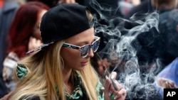 A woman smokes marijuana during the annual 4/20 marijuana gathering at Civic Center Park in downtown Denver.