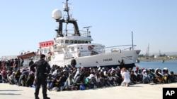 Des immigrants assis à terre après le débarquement du navire d'aide de la station migrant «Phoenix» dans le port d'Augusta, en Sicile, au sud de l'Italie, samedi 9 mai 2015.