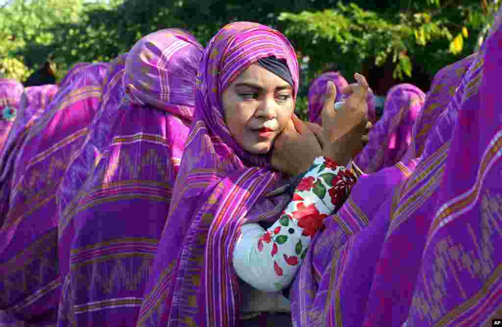 A woman adjusts her headscarf during a cultural and environmental themed parade in Bali, Indonesia.
