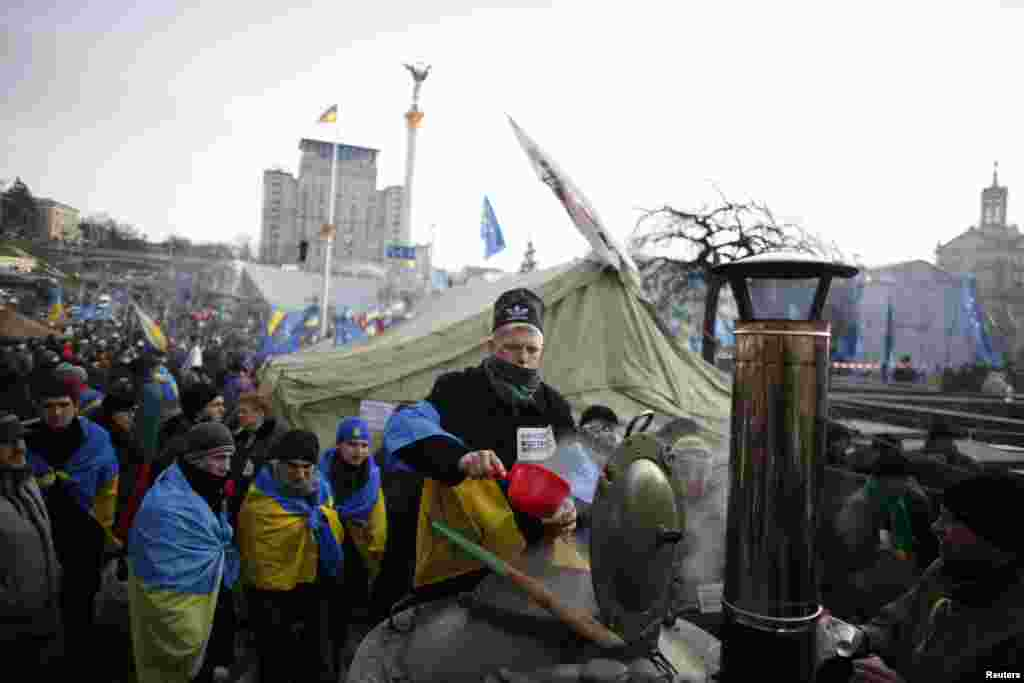 A man wrapped in a Ukrainian flag distributes tea to protesters at Independence Square in Kyiv, Dec. 4, 2013.