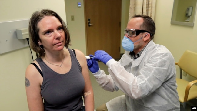 FILE - Jennifer Haller, left, receives the first shot in the first-stage safety study clinical trial of a potential vaccine for COVID-19, March 16, 2020, at the Kaiser Permanente Washington Health Research Institute in Seattle. (AP Photo/Ted S. Warren)