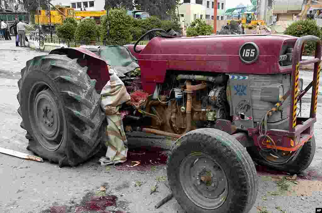 Pools of blood are seen near a damaged tractor at the site where two bombs detonated in Idlib. (Reuters/SANA)