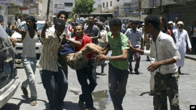 Anti-government protesters carry a fellow protester wounded during clashes with police in the southern Yemeni port city of Aden, April 30, 2011