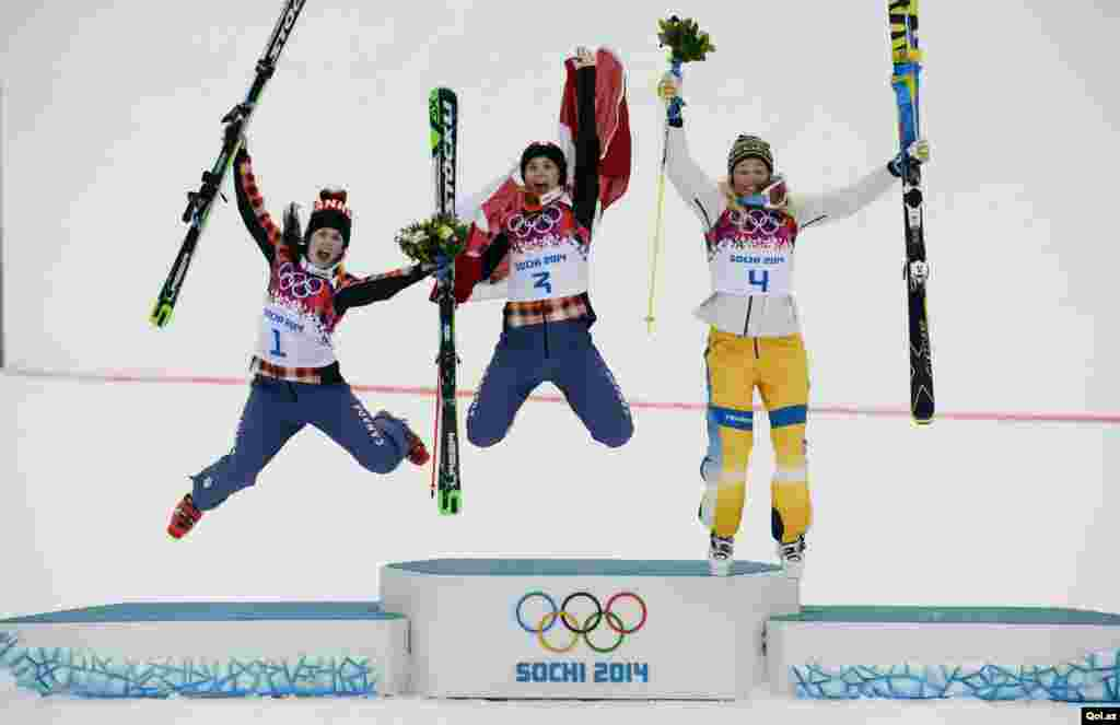 Canada's winner Marielle Thompson, second-placed compatriot Kelsey Serwa, and Sweden's third-placed Anna Holmlund (L-R) jump on the podium after the women's freestyle skicross finals at the 2014 Sochi Winter Olympic Games in in Rosa Khutor, Russia.
