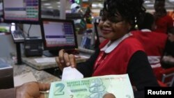 FILE: A till operator poses with new bond notes at a supermarket in Harare, Nov. 28, 2016.