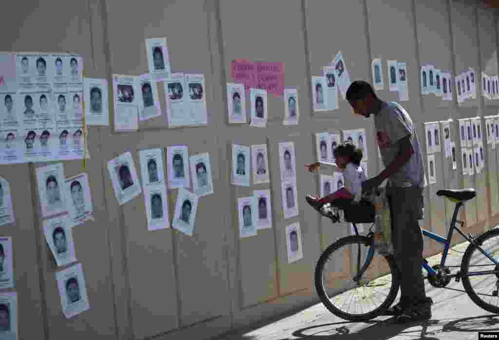 A girl points at photographs of missing students from the Ayotzinapa teachers' training college, on a wall surrounding the General Attorney's Office in Ciudad Juarez, Oct. 23, 2014.