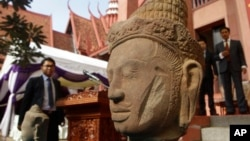 The head of Male Divinity statue is on display during a ceremony after the artifacts were returned back from Norwegian collector Morten Bosterud, at Cambodian National Museum in Phnom Penh, Cambodia, Tuesday, Oct. 20, 2015. Cambodia welcomed home two stone statue from golden Angkor era that was looted from a temple during the country's civil war and spent the past three decades in abroad. (AP Photo/Heng Sinith)