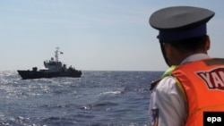 FILE - A Vietnamese coast guard officer looks at a Vietnamese coast guard vessel in the South China Sea, May 14, 2014. Vietnam has faced increasingly aggressive Chinese territorial claims to sections of the South China Sea, where Vietnamese maritime patrols have faced off against Chinese naval forces.