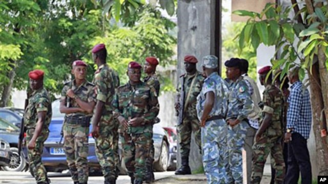 Ivorian soldiers stand guard at the entrance to electoral commission headquarters in Abidjan, 01 Dec 2010