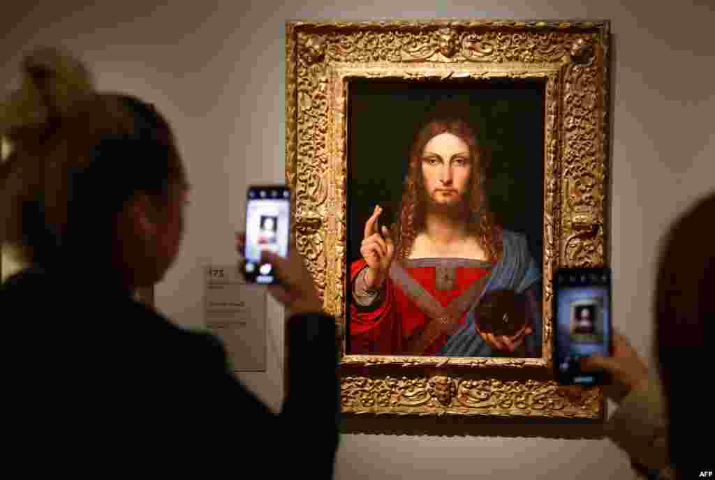 "People take pictures of an oil painting by Leonardo da Vinci's "" Salvator Mundi"" during the opening of the exhibition "" Leonardo da Vinci "" at the Louvre museum in Paris, France."