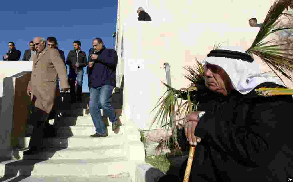 Parliamentary candidate Mahmoud al Kharabshy, left, arrives at his district polling station to observe the voting process in Al-Salt, Jordan, January 23, 2013.