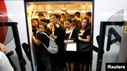 Passengers dressed in black to mourn Thailand's late King Bhumibol Adulyadej are seen in a train car during rush hours at a station in Bangkok, Thailand, Oct. 17, 2016.