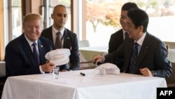 """US President Donald Trump speaks with Japan's Prime Minister Shinzo Abe during a luncheon at the Kasumigaseki Country Club Gold Course in Tokyo, Nov. 5, 2017. The president and prime minister signed white hats reading """"Donald and Shinzo Make Alliance Even"""