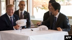 """Američki predsednik Donald Tramp razgovara sa japanskim premijerom Šinzoom Abeom tokom ručka u Kasumigaseki kantri klubu pokraj Tokija. Predsednik i premijer potpsali su se na kape na kojima piše """"Donald i Šinzo prave savezništvo još većim""""."""