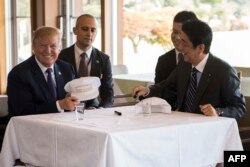 US President Donald Trump speaks with Japan's Prime Minister Shinzo Abe during a luncheon at the Kasumigaseki Country Club Gold Course in Tokyo, Nov. 5, 2017.