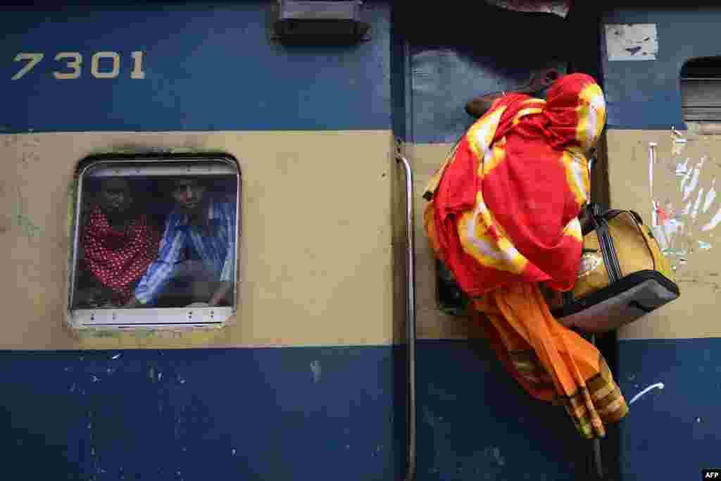 A Bangladeshi passenger climbs on top of a train as other passengers (R) look on from a compartment window as they rush home to their respective villages to be with their families ahead of the Muslim festival of Eid al-Fitr, in Dhaka.