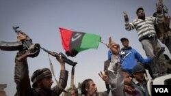 Pemberontak Libya menari-nari merayakan kemenangan setelah merebut kota Ajdabiya, di selatan Benghazi, Sabtu (26/3).