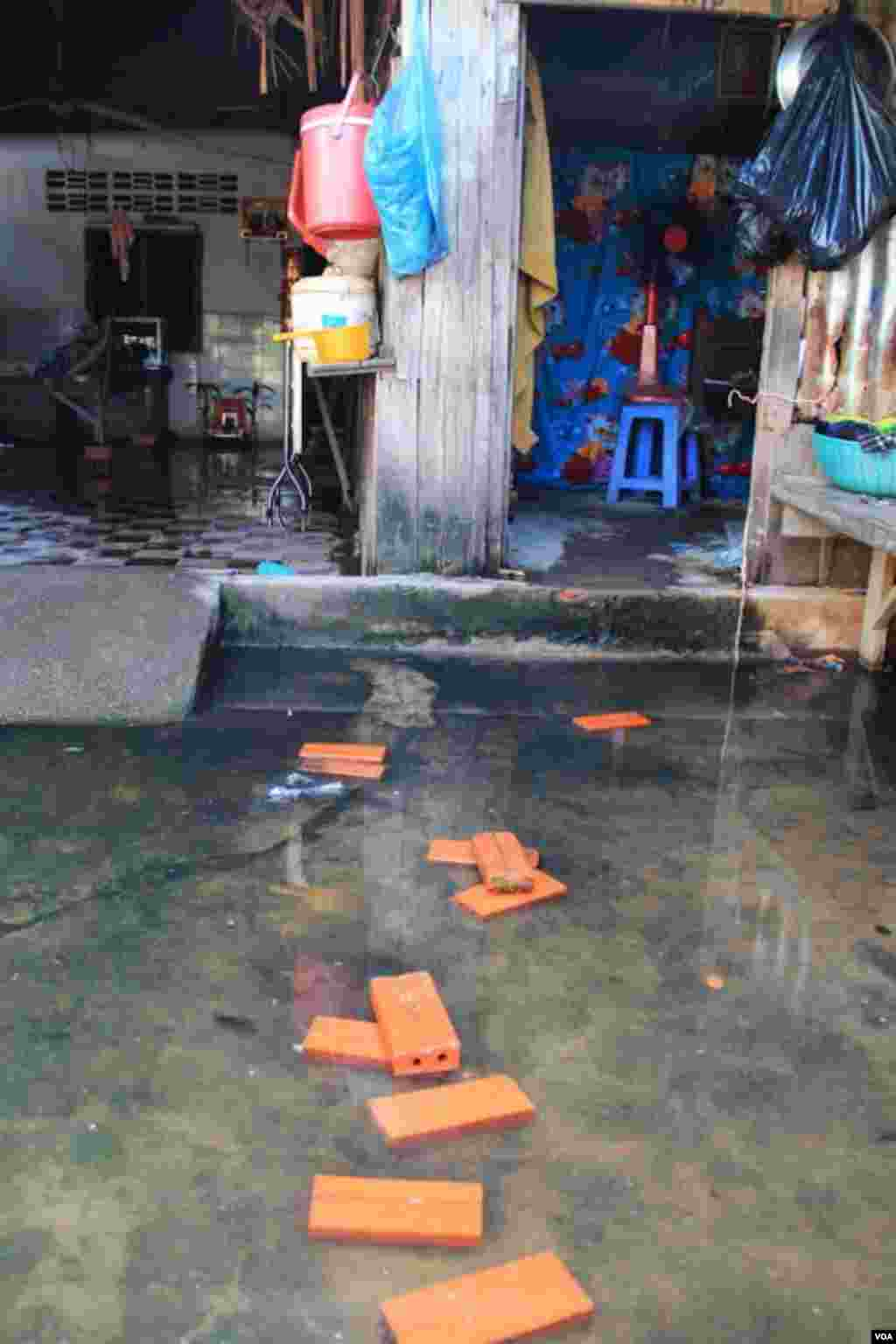 The flood water from the rain is still there in front of Khoeun Sovat's house in Boeung Kak community in Phnom Penh, Cambodia, Nov. 13, 2014. (Nov Povleakhena/VOA Khmer)