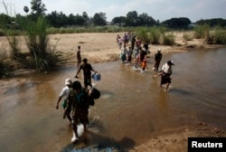 FILE - A group of Myanmar refugees, who crossed over from Myanmar to Thailand when a battle erupted between Myanmar's soldiers and rebels, walk across a stream of water at the Thai border town of Mae Sot, Nov. 8, 2010.