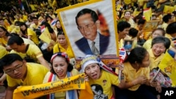 FILE - Supporters of Thailand's King Bhumibol Adulyadej, carrying portraits and banners, are seen celebarting his 87th birthday, in Bangkok, Thailand, Dec. 5, 2014.