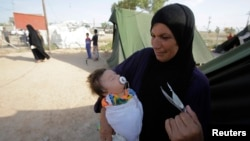 FILE- A woman who fled violence in the Iraqi town of Jalawla carries a baby at Ali Awa refugee camp, near Khanaqin city, Aug. 28, 2014.