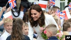 FILE - Children welcome Britain's Kate, the Duchess of Cambridge, during her visit with Prince William in front of the presidential palace, in Warsaw, Poland, July 17, 2017.