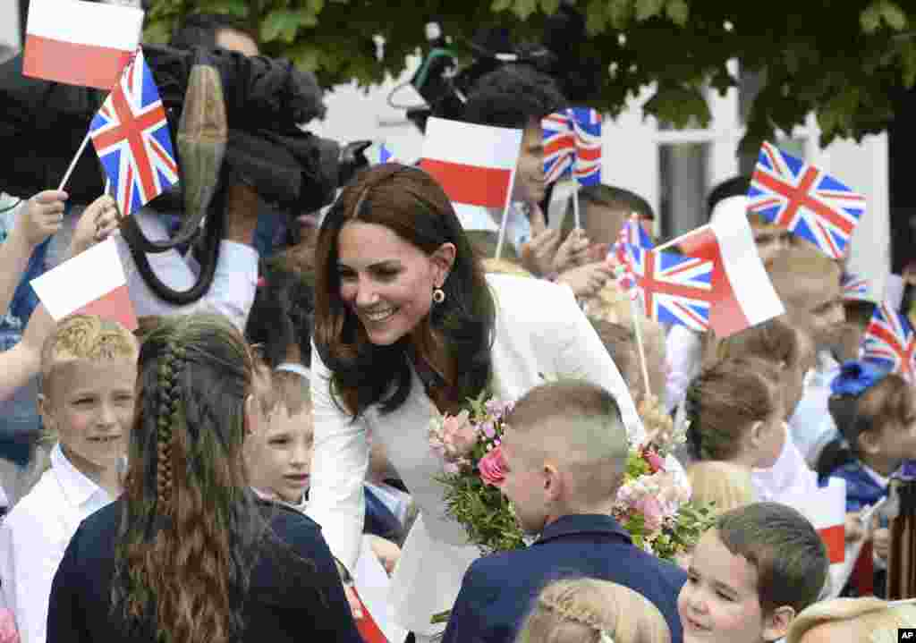 Children welcome Britain's Kate, the Duchess of Cambridge, during her visit with Prince William in front of the presidential palace, in Warsaw, Poland.