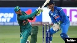 شعیب ملک بھارت کے خلاف شارٹ کھیلتے ہوئے، پس منظر میں دھونی نظر آرہے ہیں