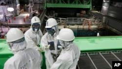 Сотрудники Tokyo Electric Power Co. (TEPCO) и журналисты в защитных костюмах смотрят в бассейн с топливными стержнями в здании четвертого реактора на АЭС «Фукусима». Префектура Фукусима. Япония. 7 ноября 2013 г.