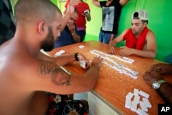 Cuban migrants play dominoes to pass the time at a temporary shelter in La Cruz, Costa Rica, Jan. 12, 2016.